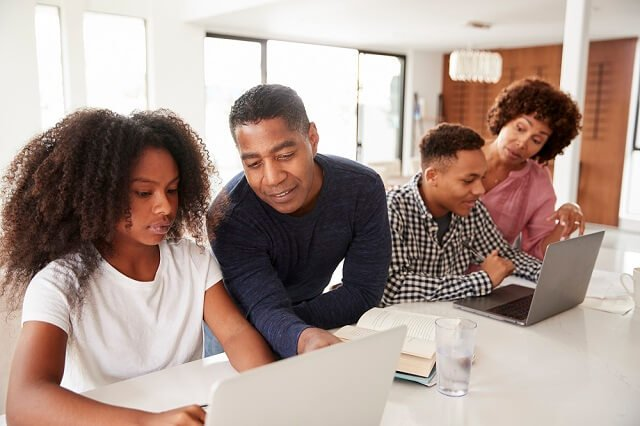 family looking at laptops together medium