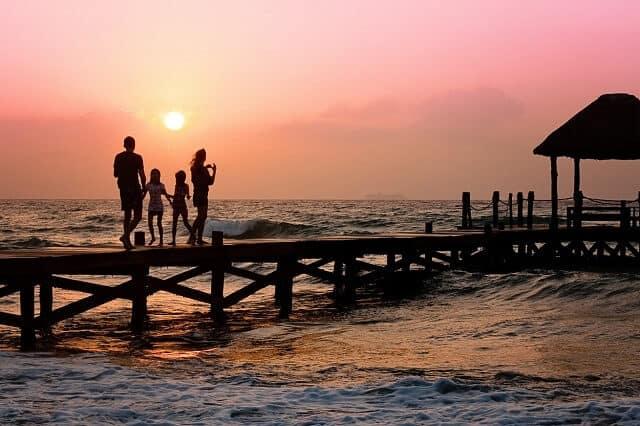 family walking along pier sunset