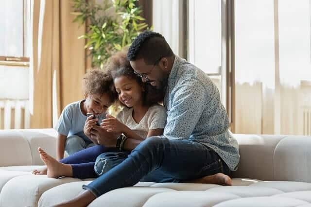 father with children on smartphone medium