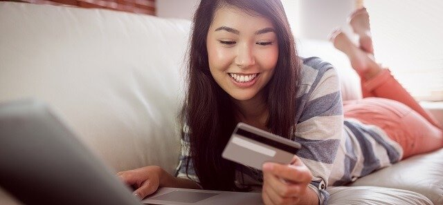 girl on couch with card and laptop smiling
