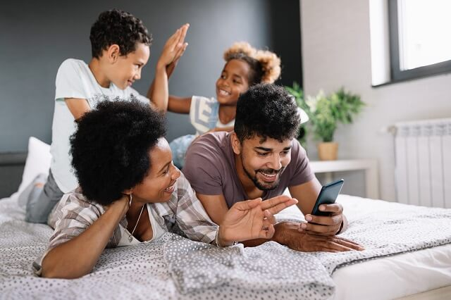 happy family on the bed with smartphone