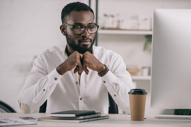 man looking at computer with investments medium