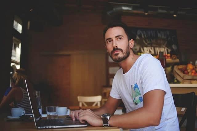 man sitting at laptop thinking medium