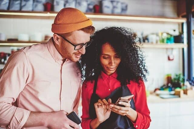 millennial couple looking at smartphone medium