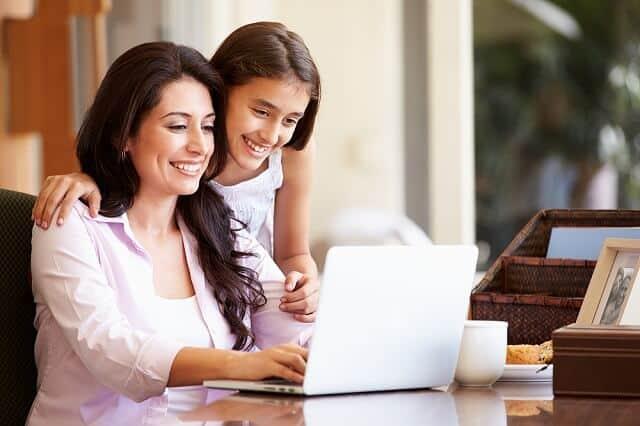 mother and daughter using laptop smiling medium