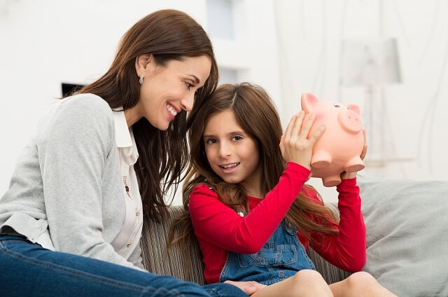 mother and daughter piggy bank smiling