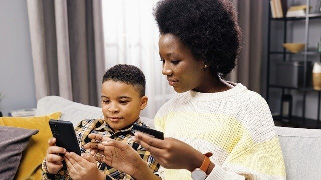 mother and son using a debit card on a phone