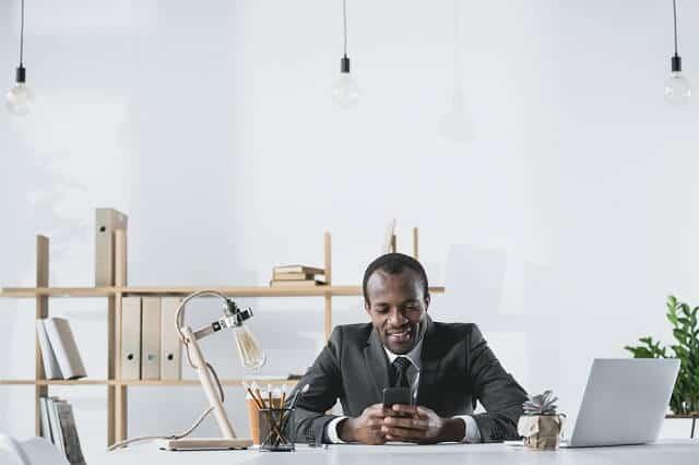 successful man looking at phone medium