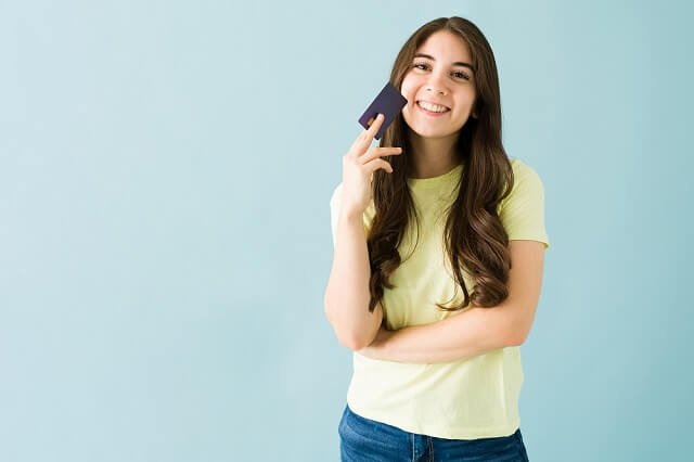 teenage girl with credit card happy