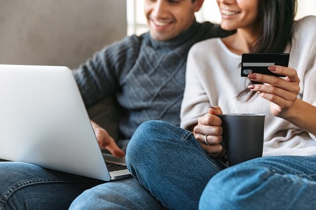 young couple with credit card and coffee on couch