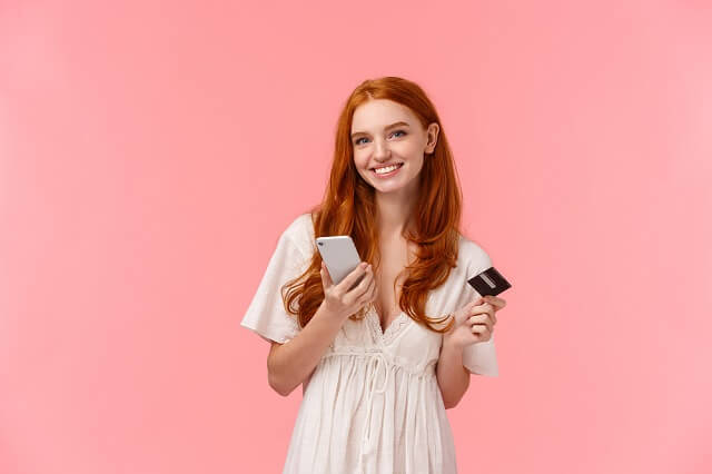young woman smiling with credit card and smartphone